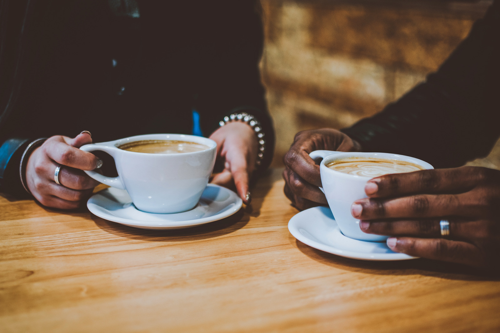 Two people sat holding mugs of coffee