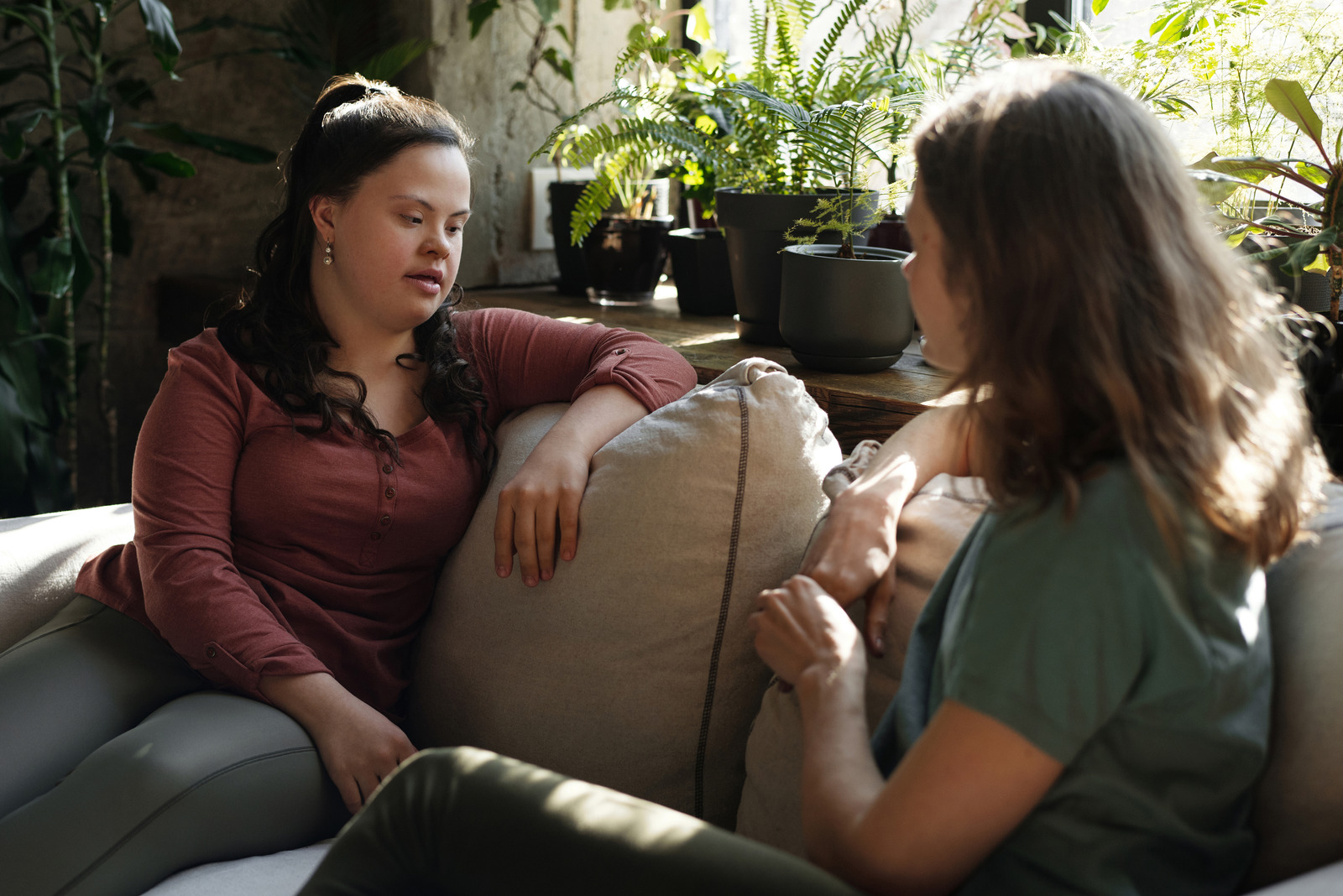 Two women face each other on a sofa talking