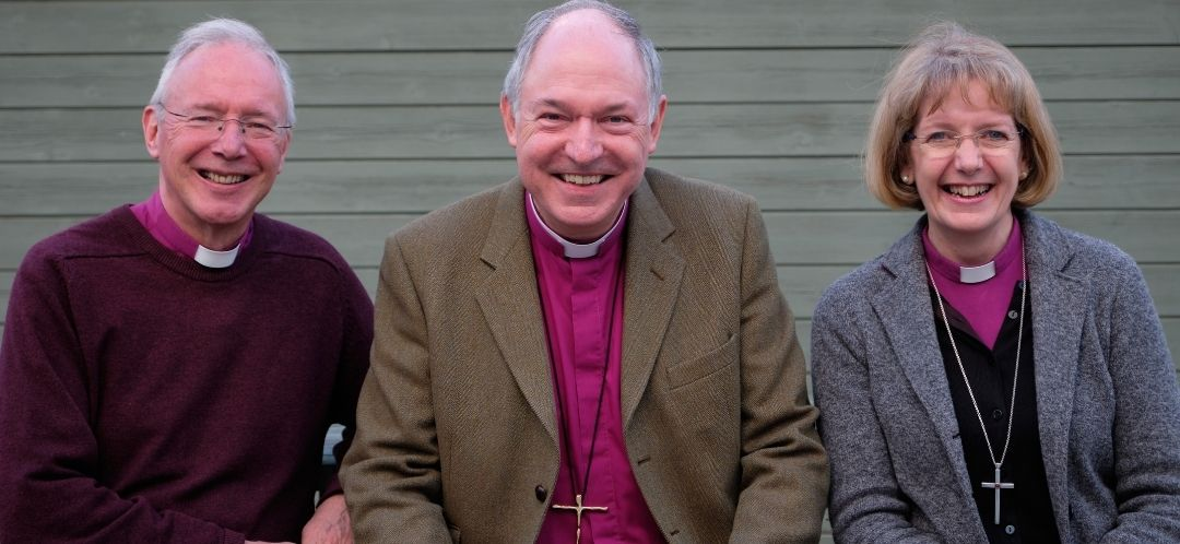 The three bishops sat next to each other smiling