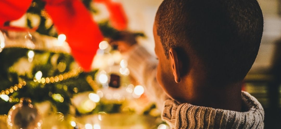 A boy hangs a Christmas decoration on a Christmas tree