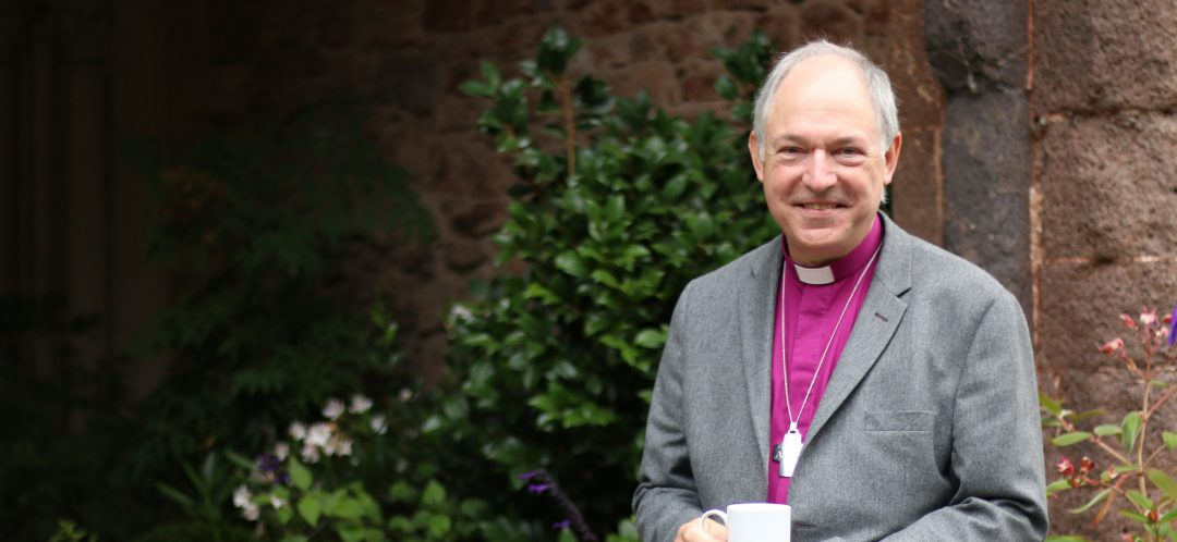 Bishop Robert smiling with a mug of coffee in his hand